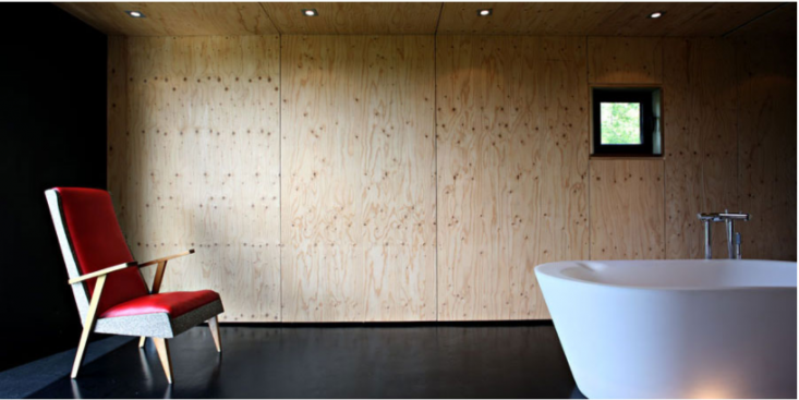 The main living space is anchored by an Italian-made LTT Illuminated Bathtub positioned next to a wood-burning stove.