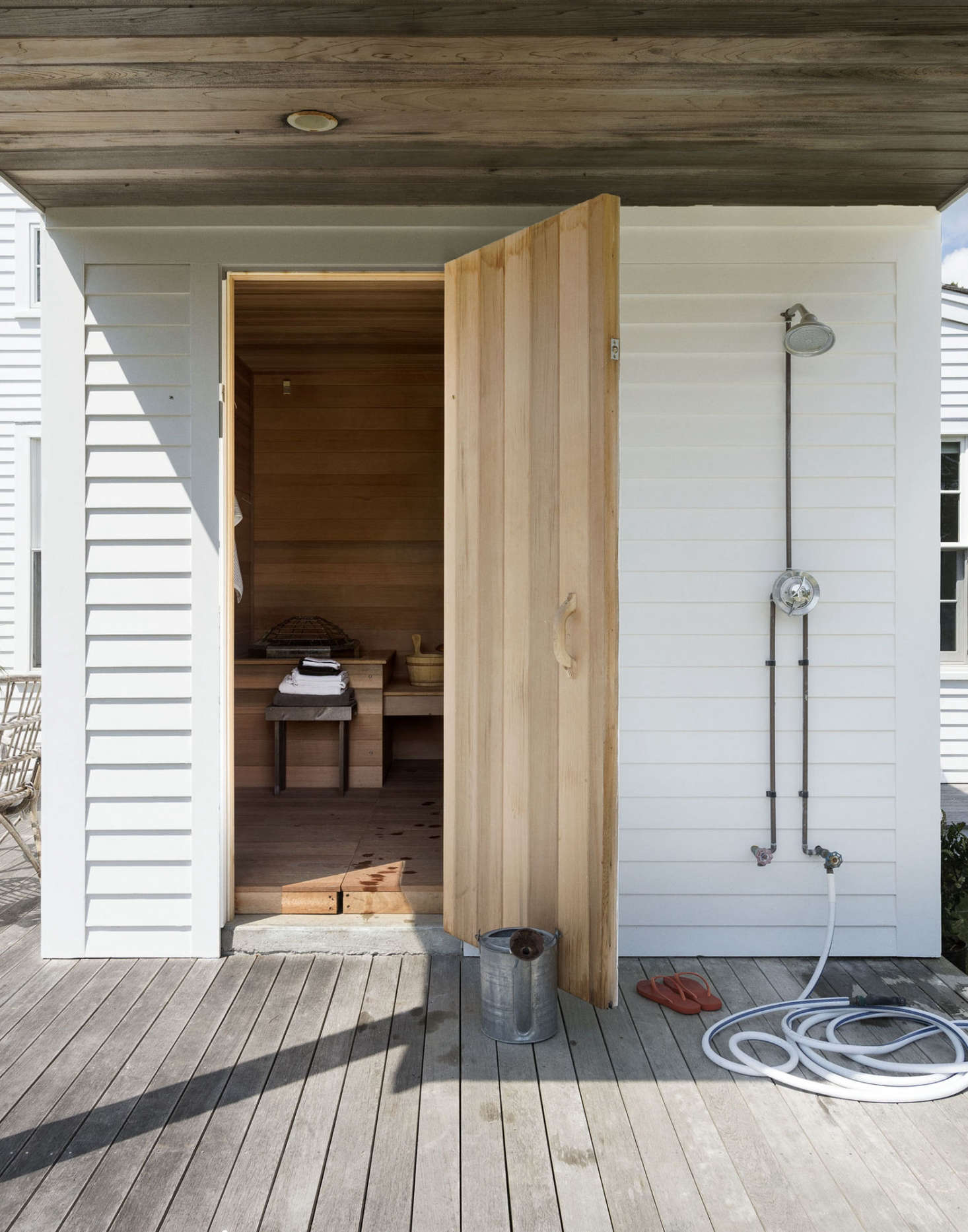 A Maine summer necessity: an unfussy outdoor shower for washing off sunscreen and sand at the end of the day. It can be simple: an exposed pipe and some slatted wood to stand on, as shown here, will do. Photograph by Matthew Williams for the Gardenista book, as seen in  Favorites: Outdoor Showers.