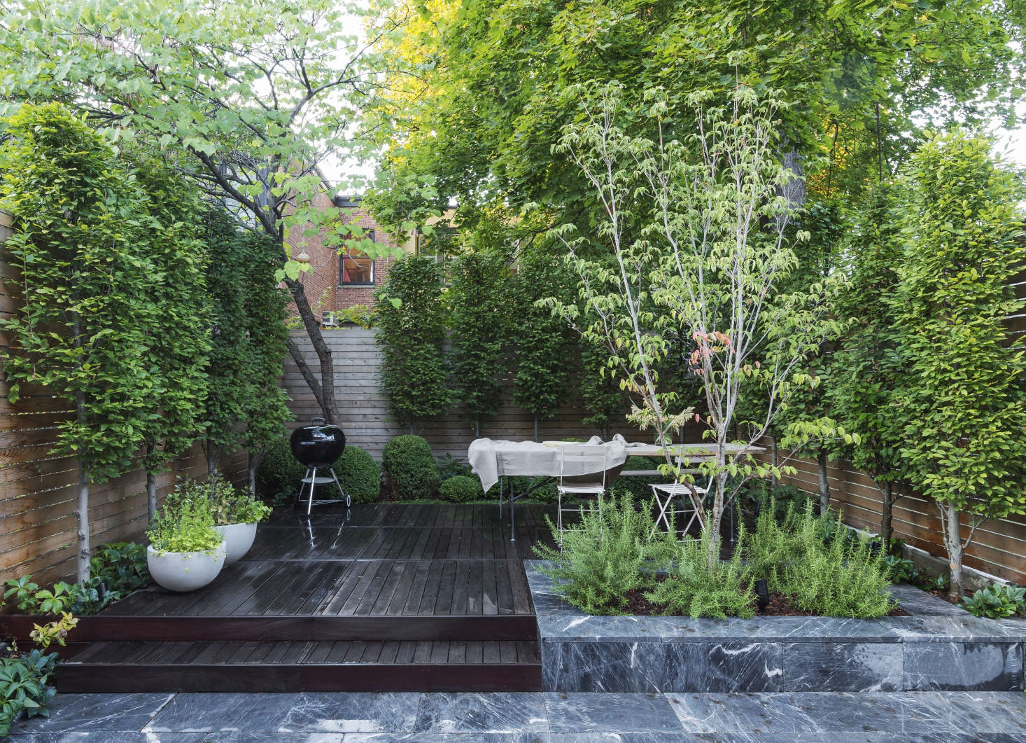 Garden designer Brook Klausing paired imported marble pavers with wooden decking to set off their striking variation in pattern in color in a small Brooklyn backyard. Photograph by Matthew Williams for Gardenista.