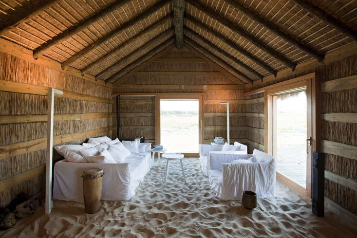 The beach accompanies you indoors at Casas Na Areia, a compound of four cottages an hour south of Lisbon. In addition to the sand floor, construction materials include local wood and reeds. Photograph by Nelson Garrido.