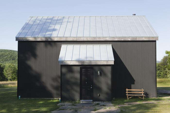 The exterior of ath-century barn is clad in black corrugated aluminum. The standing seam aluminum roof is typical of the vernacular architecture in this part of New York. There are no windows on the front facade to keep insulation factors at their highest. Photograph by Torkil Stavdal.