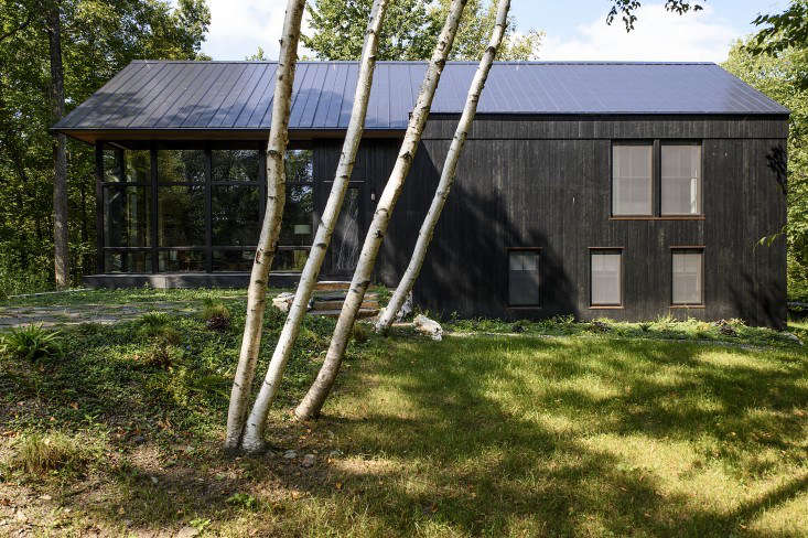 Carefully sited to minimize the need to remove existing trees, the main house relates to the contours of the land. Using traditional Japanese shou-sugi-ban techniques, the facade's cedar siding was burned, brushed, washed, and oiled to achieve its charred look. Photograph by Reto Guntli except where noted, courtesy of BarlisWedlick Architects.