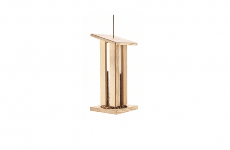 A Bird Feeder Made From Ash Wood has a wooden frame surrounding an acrylic glass feeder tube to keep bird seed dry in inclement weather. It is €6\2 from Manufactum.