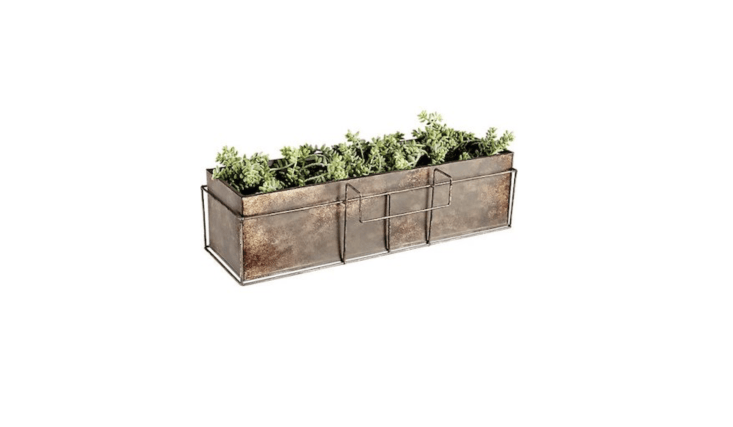 A Girona Patina Rectangular Rail Planter made of galvanized steel and coated in nontoxic paint is \$\26.95 from CB\2. Sold separately, a galvanized steel Rectangular Rail Planter Frame is \$\1\2.95.