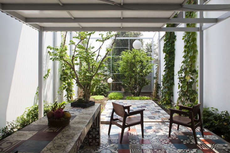 By putting colorful patchwork tile on nearly every inch of the walls and floors of a tiny house's open-air kitchen and courtyard garden, Vietnam-based architects a