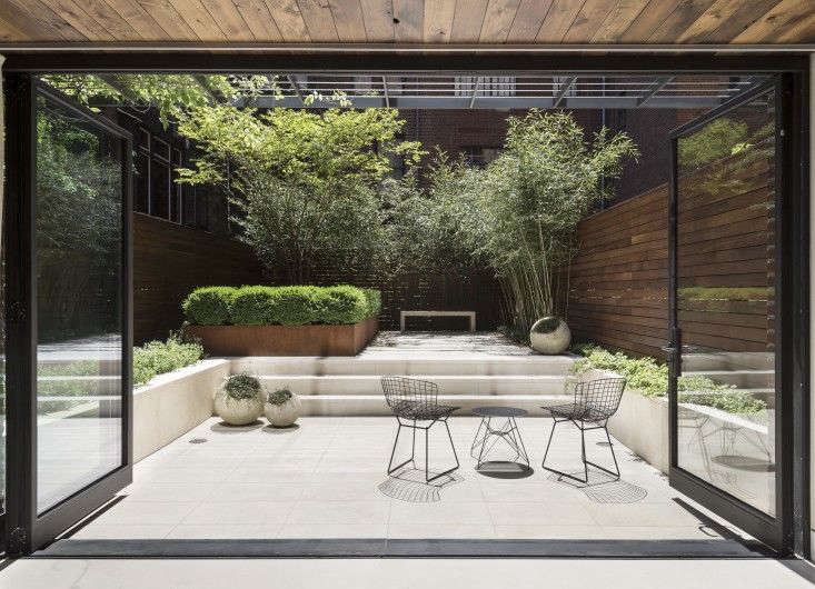 """In Manhattan, an airy hedge of bamboo provides screening at the garden's perimeter while a pared-down palette of green and white focuses the eye on the center of the space. """"The white limestone is like a canvas. When the sun is directly overhead, you can see the shadows of the bamboo and other plants starkly against it,"""" says designer Julie Farris. Photograph by Matthew Williams."""