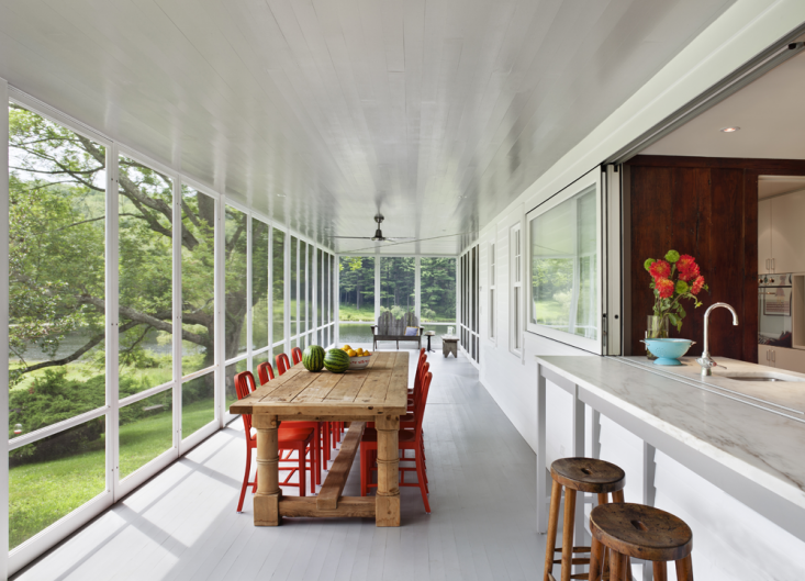 The screened porch can become a glazed porch and becomes usable for three seasons; sometimes even in the winter when the weather is mild, which gives the family more space during the winter and yet retaining its airiness in the summer. Photograph by Michael Moran, from The Architect Is In: Porch Appreciation in Connecticut.