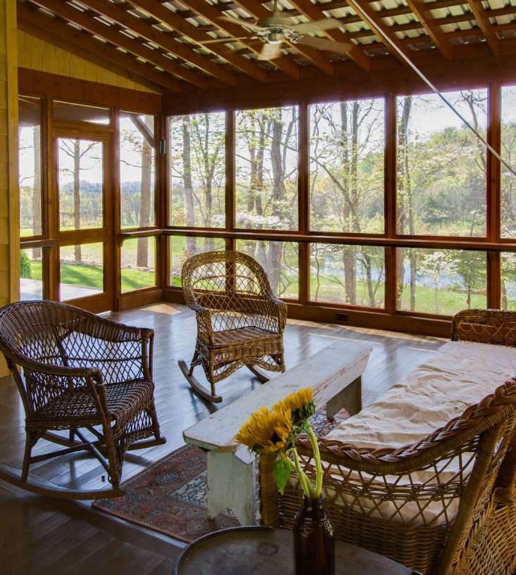 """This screened porch is one of four porches in this home. """"It is a bit unusual to build so many porches on a new residence as budget constraints and modern air conditioning usually rule out all but the most modest examples,"""" says the architect. """"However, the desire to live indoors/outdoors made them essential."""" Photography by Ruth and Marcus Di Pietro, from The Architect Is In: Romancing the Country in Nashville, Music and Porches Included."""
