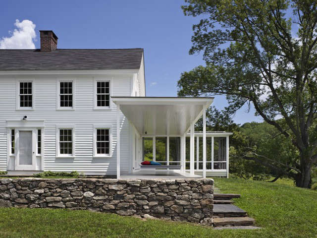 A minimalist modern porch and a traditional stone wall are the perfect pairing for this Connecticut long house. Photograph by Michael Moran, from The Architect Is In: Porch Appreciation in Connecticut.