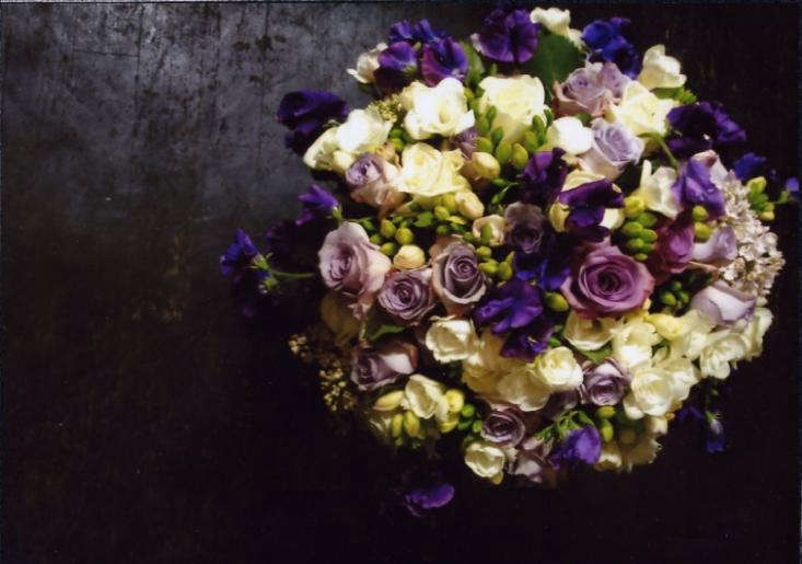 A mass of roses and freesias, arranged together to heighten their complementary fragrances.