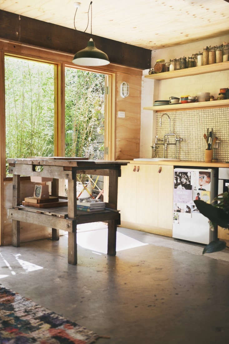 Melbourne, Australia-based Hearth Studio turned a garage into a small home complete with kitchen, dining area, bedroom, and bath (with green clawfoot tub). The designers managed to fit it all in while retaining the character of the garage, including its hardworking concrete floor. For more, see Outbuilding of the Week: Garage Turned Studio Apartment. Photograph by Lauren Bamford.