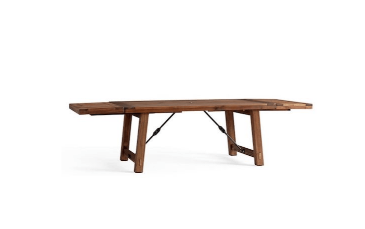 A74-inch-long Benchwright Extending Dining Table is made of solid acacia wood and has adjustable levelers to keep it steady on uneven ground; on sale for \$\1,499 from Pottery Barn.