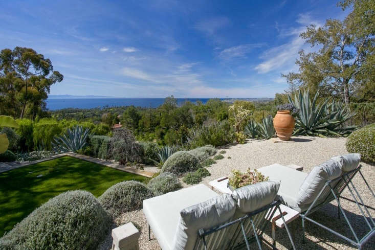 An elevated terrace paved with light-colored gravel that feels cool underfoot even in hot sun, Ellen DeGeneres and Portia de Rossi have a view in Santa Barbara that stretches to the Pacific Ocean. Their 30s Montecito, CA villa is for sale for $45 million. Photograph via Realtor.