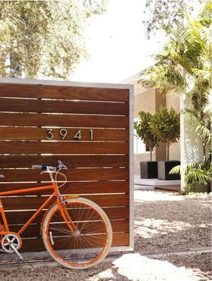 Photograph via Design Within Reach.Neutra house numbers and a pea gravel path. For more, see5 Favorites: Modern Wooden Gates.