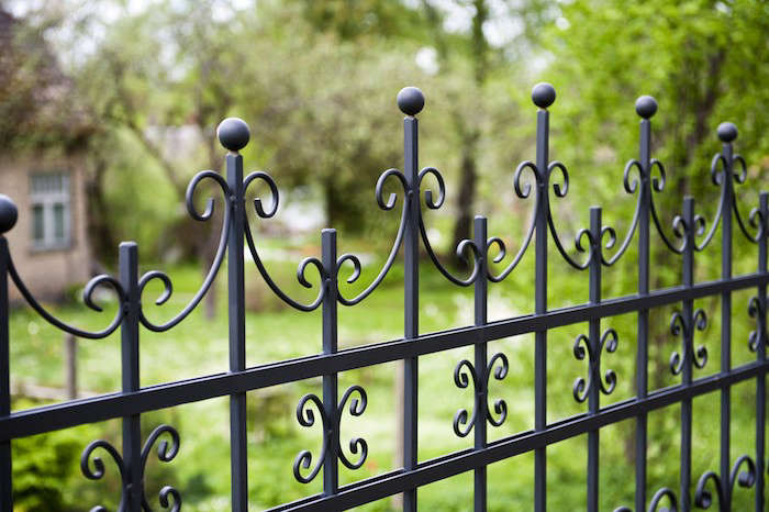 Made of powder-coated steel, Ornamental Steel fence panels from Hercules Fence are available in several styles and custom colors as well as standard (white, black, dark green, and bronze). Photograph via Hercules Fence.