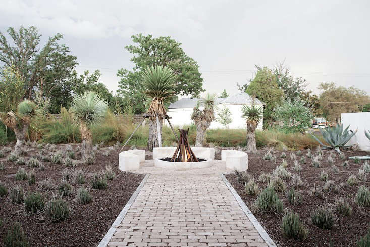 Hill used reclaimed bricks to create a path leading to a circular fire pitwith built-in seatingand a gas-powered campfire sculpture made of salvaged pipes byartist George Sacaris. Photograph by Misty Keasler via Dwell.
