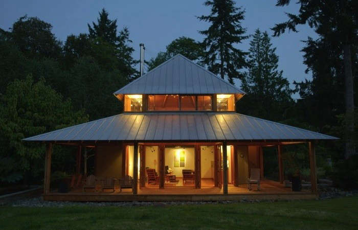 For a cabin in Hansville, Washington, Rohleder Borges Architecture installed a simple gutter-less standing seam roof made of galvanized metal. Rainwater runs down to a bed of river rock below. Image by Cynthia Grabau Photography.