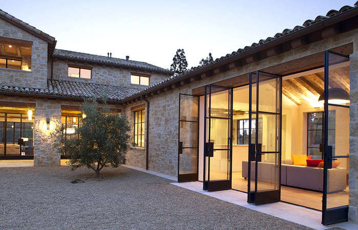 Traditional materials–stone and clay barrel roof tiles–come together in a modern setting in this house by Bay Area architect Ken Linsteadt. Photograph courtesy of Ken Linsteadt.