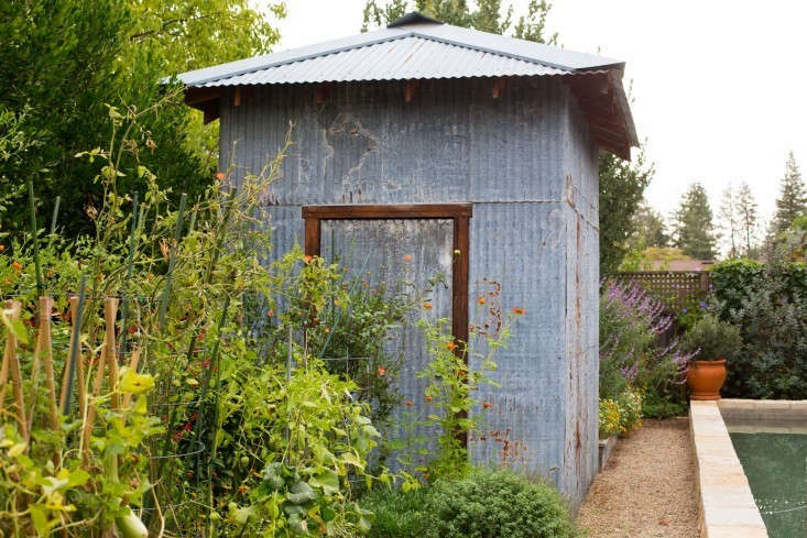 Recycled materials such as corrugated metal siding can be transformed into charming garden sheds. See more at Outbuilding of the Week: A Salvaged Shed in a Napa Garden. Photograph by Mimi Giboin.