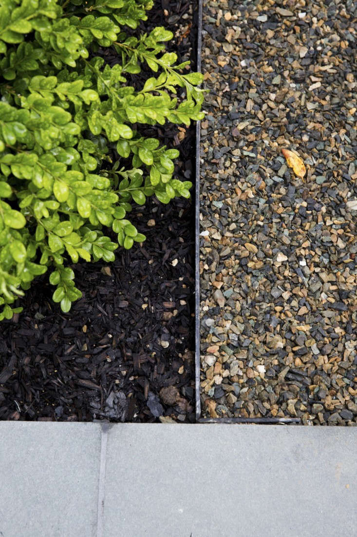 A pea-gravel path abuts a bed of mulch and bluestone pavers, neatly separated by a strip of metal edging. Photograph by Nicole Franzen for Gardenista.