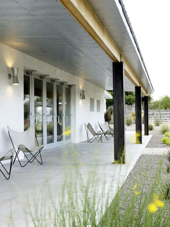 In the open-air breezeway, a row of butterfly chairs. The underside of the eaves is clad in aluminum/zinc Home Depot-sourcedGalvalume panels. A simple polished-concrete slab serves as deck. Photograph courtesy of Barbara Hill Design.
