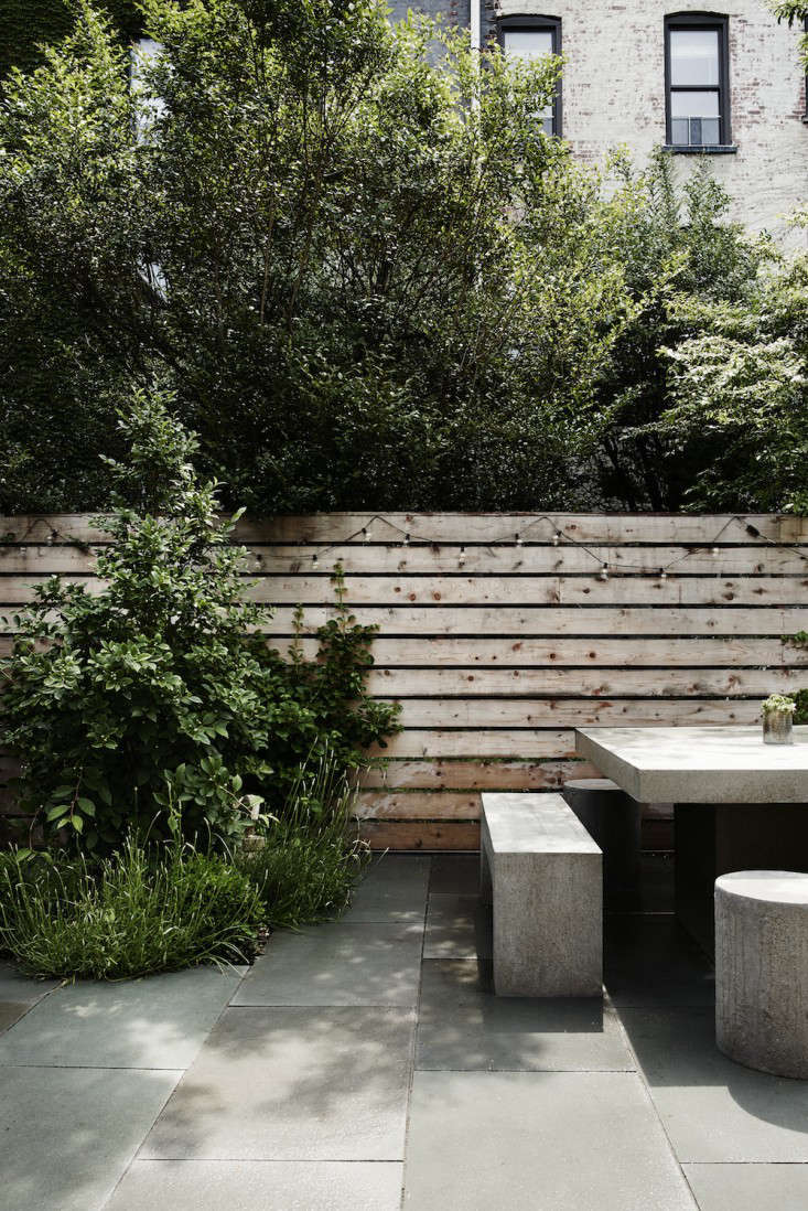 """In a Brooklyn garden, designer Lindsey Taylor left acedar fence unstained; it will weather to a soft gray and then be sealed. &#8\2\20;Space between the horizontal slats is good for circulation. """"There is a problem with mosquitos in Brooklyn, so we wanted a lot of good air flow and its better for the health ofthe plants,"""" says Lindsey. For more, see Before & After: A Modern Townhouse Garden in Brooklyn. Photograph by Pia Ulin via Bangia Agostinho Architecture."""
