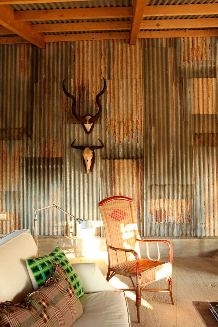 Interior walls are sided with reclaimed corrugated metal panels, recycled from a chicken coop.