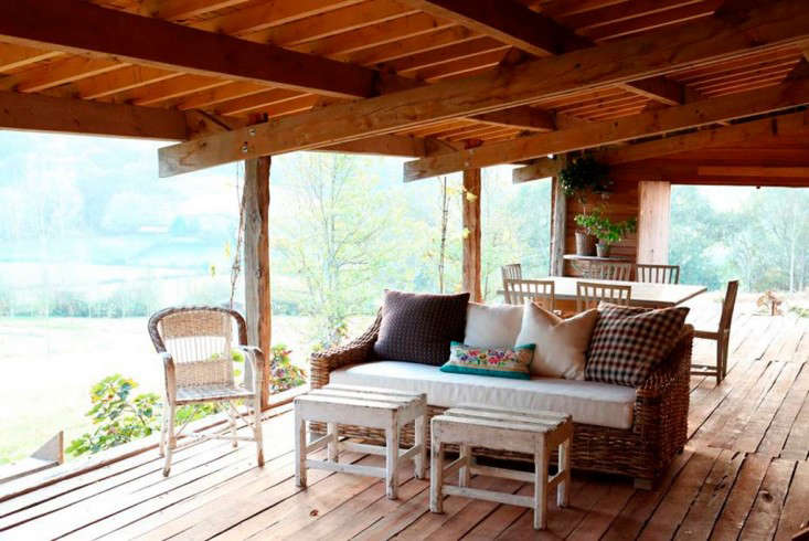 A peaked roof of pine beams covers the porch.