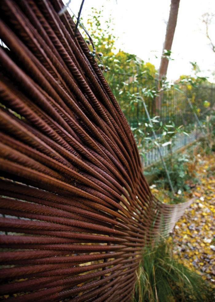 In Edinburgh, Scotland, architects Groves-Raines used traditional Scottish willow weaving techniques to create a rusty barrier around a custom composting shed from A New World Composting Shed in Edinburgh.Photograph by Dan Farrarcourtesy of Groves-Raines Architects