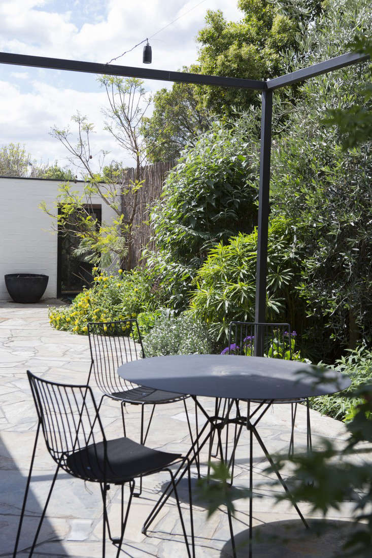 In the backyard is a patio with crazy paved slate and an open-air pergola with suspended lighting. Designer Stephanie Paterson sourced the furniture, including a Tio Dining Table and Tio Chairs  by Stockholm-based designer Massproductions.