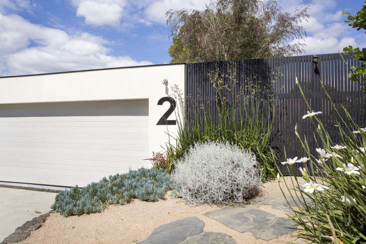 The large house number on the garage is stencil-cut steel. Next to the driveway, a front path set with free-form bluestone pavers is lined by drought-tolerant plants including Anigozanthos (commonly known as kangaroo paw), a silver bush of Leucophyta brownii, and Dieties Iridiodies (African iris).
