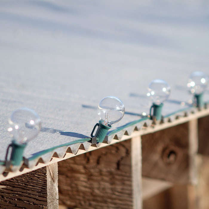 Using aluminum gutter clips (or, in a pinch, document binder clips) is an easy way to attach light strings to a roof line. A bag of 50 Gutter Hooks is $.95 at Holiday Light Hooks. Photograph via Terrain.