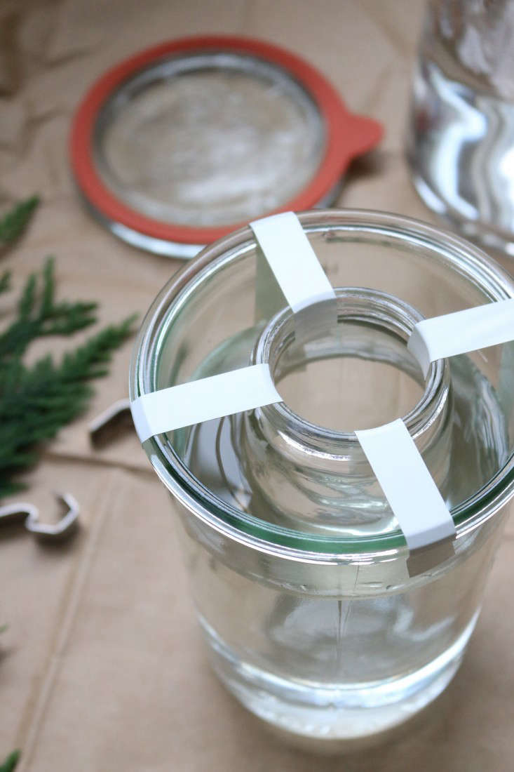 Use electrical tape to center the smaller container inside the larger one. The water will keep the the container afloat, but you&#8