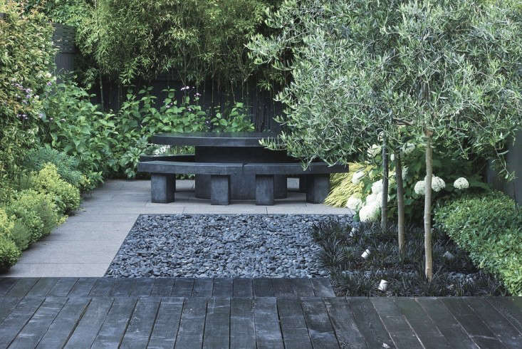 In the back of the garden, a table and benches for seating draws the eye to a distant destination. Along the back fence is planted a stand of black-stemmed bamboo (Phyllostachys nigra).