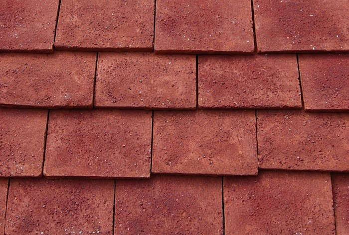 Traditional Flat Clay Tiles in a red textured finish have been laid in a staggered pattern similar to that used with shingles. Photograph courtesy of Keymer Clay Tiles.