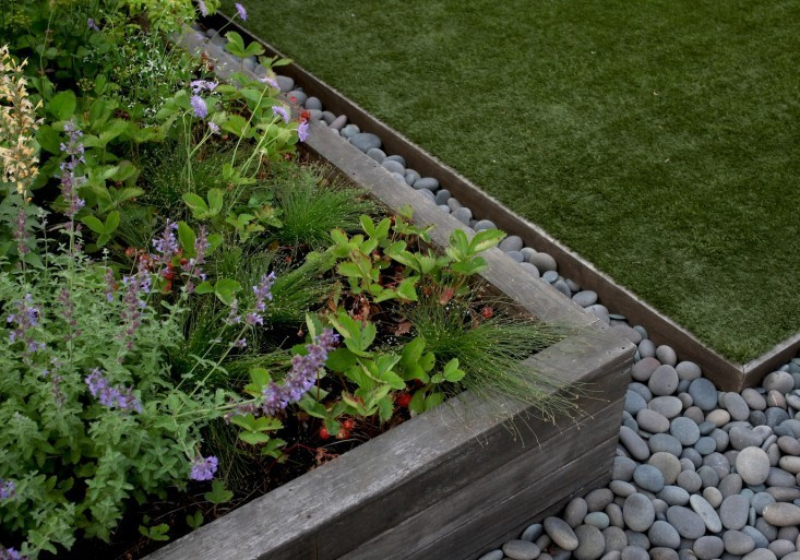 In Brooklyn, garden designer Julie Farris uses metal landscape edging and river rocks to border the raised beds on her rooftop garden. Photograph bySophia Moreno-Bungefor Gardenista.