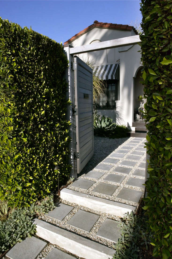 Seen from the street, a freestanding ficus hedge plays fence, to hide the facade of the Spanish revival style house. &#8