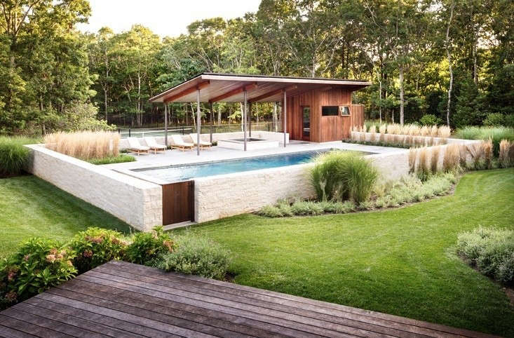Hardy native perennial plantings help soften the required pool fence, here of limestone, and add some interest to the view from the main house at A Modern Pool Pavilion in Water Mill. Photograph by John Porcheddu, courtesy of Khanna Schultz.