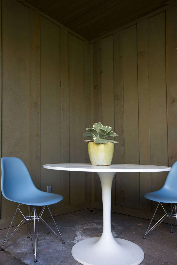 An Ikea Doksta Table in the corner of the courtyard with two two Eames Chairs from DWR.