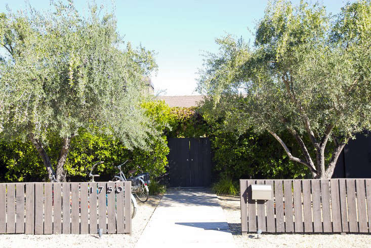 The house is set behind a low fence; the graveled patio is used for bike parking.
