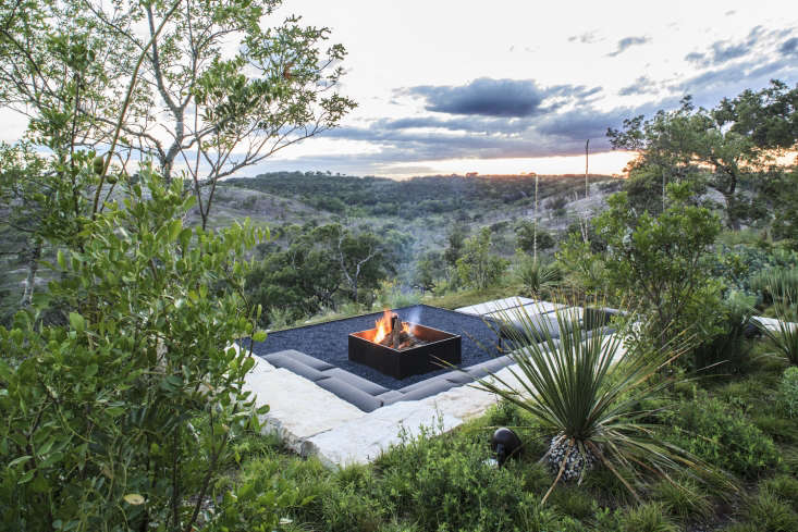 Sectional seating by Gloster has a low profile to focus attention on the fire pit. A permeable black gravel patio surrounds the pit.