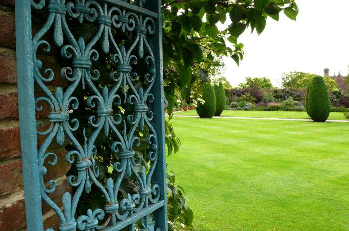 A gate at Sissinghurst Castle, painted a lively blue. This color would have been chosen in the 30s when the Nicolsons created the garden, as a nod to an earlier palette. Photograph by Kendra Wilson.