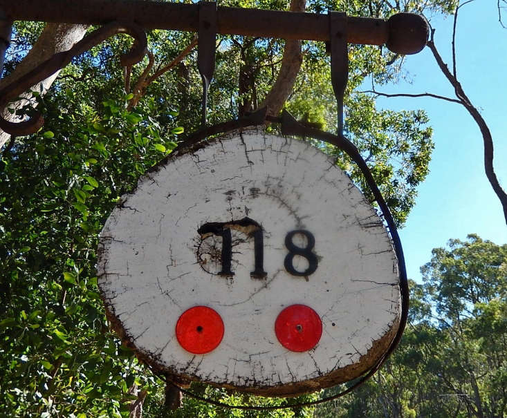 Rustic rules. House numbers are mounted on a slice of painted tree stump. Photograph by Michael Coghlan via Flickr.