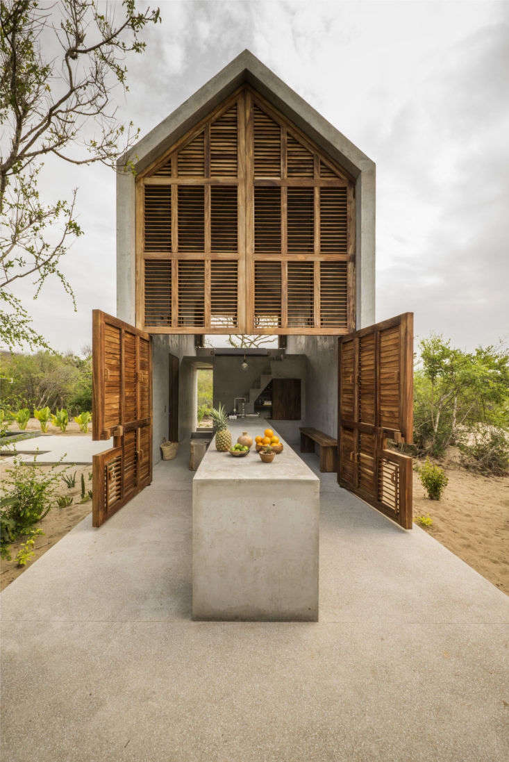 A cast concrete table extends from indoors to out in a minimalist hideaway constructed of concrete and parota wood. Photograph by Camila Cossio. For more of this project, see One Bedroom, Desert View: A Tiny Airbnb Casita in Mexico.