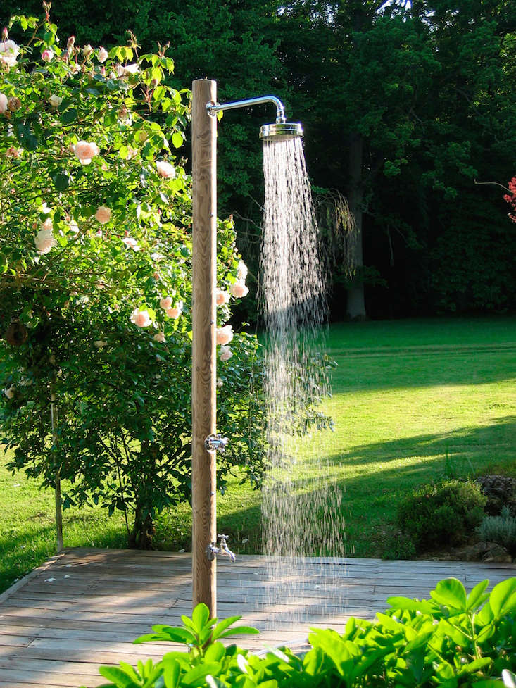A Pilotis outdoor shower made of northern pine logs has a tap to turn on for a foot wash and a faucet to connect a watering hose; for information and pricing, see Douches de Jardins.