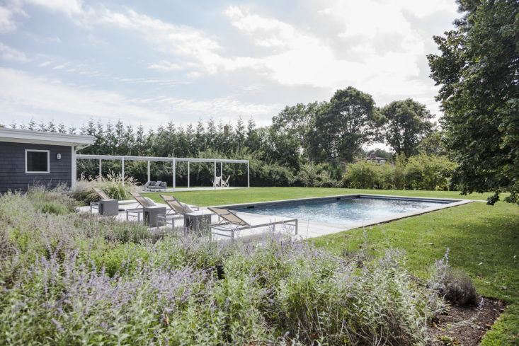 Architect Maria Milans del Bosch created a series of outdoor rooms—a pool area and a long veranda, shaded by airy shade sails, plus an outdoor kitchen—that flow seamlessly, indoors to out, for hot summer days in the Hamptons. Photograph by Montse Zamorano.
