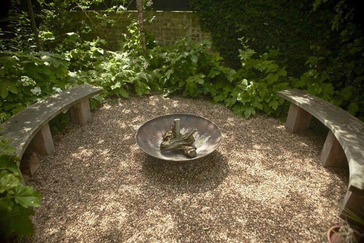 """Photograph by Jim Powell for Gardenista.Surrounded by woodland, a gravel seating circle surrounds a fire pit and provides a buffer between sparksand the garden. For more of this project, see Lessons Learned: From """"Neglected"""" Slope to Charming Garden, in South London."""