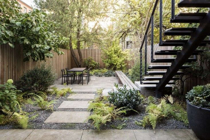 "In a Brooklyn backyard, designer Brook Klausing edged limestone pavers with crushed limestone dust mixed with gravel. ""It's a very modern look, but I tried to soften it with the gravel and plantings, like the ferns in the gravel,"" says Klausing. For more of this garden, see Designer Visit: Brook Klausing Elevates a Brooklyn Backyard."