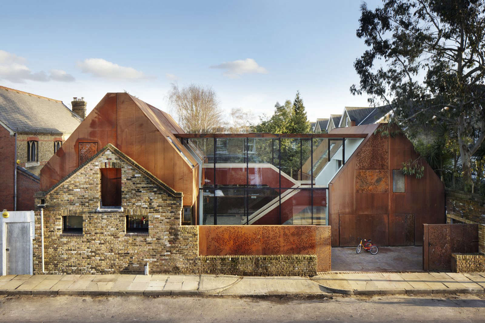 Architects Piercy & Company designed a perforated steel fence to let light into a brick-paved courtyard and to visually connect the two gabled wings of a house built behind the facade of a Victorian stables in London. Photograph via The Modern House.