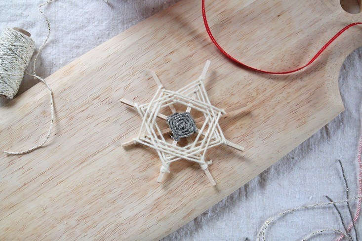 You can also alternate the yarns that form the squares to create a radiating snowflake look. To do this, begin as you did above with two pieces of string tied to consecutive sticks. Work one string around the square, but don&#8